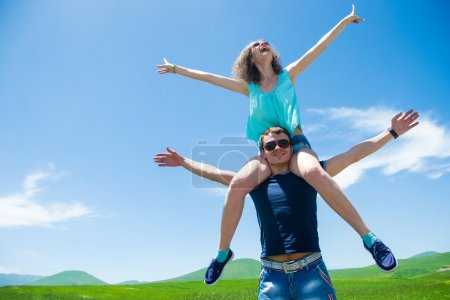 happy couple with open arms, girl sitting on shoulders man