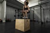 Girl performing box jumps in the gy