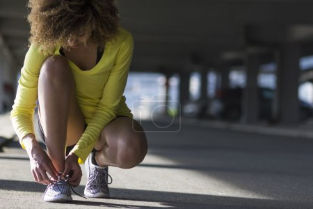 Photo for Mixed race girl fixing her shoulace while stretching - Royalty Free Image