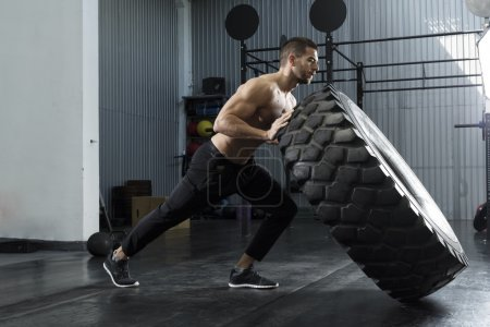 Bodybuilder flipping tire at the gym