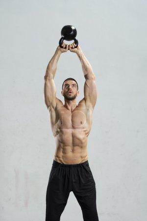 Bodybuilder doing wall ball exercise