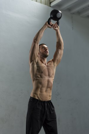 Bodybuilder doing wall ball exercise