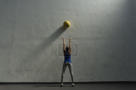 Woman doing wall ball exercise