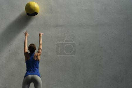 Woman doing wall ball exercise