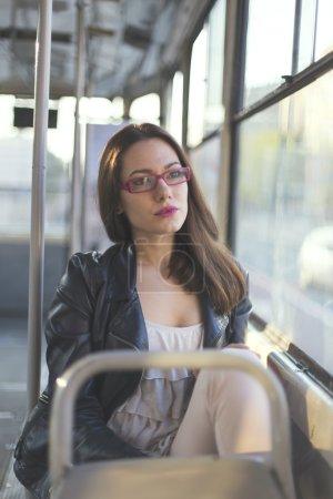 Girl looking thru a window on a bus