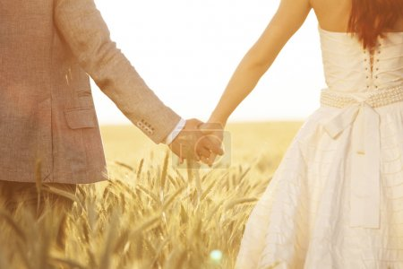 Close up shot of newlyweds holding hands...