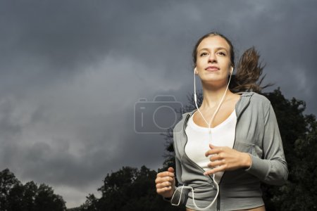 Attractive girl jogging in the park before storm