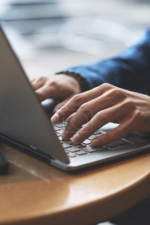 Photo for Side view of human hands typing on laptop - Royalty Free Image