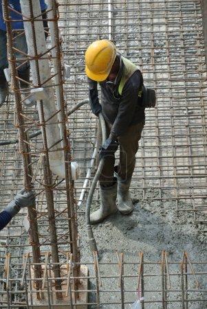 Photo pour Travailleur de la construction utilisant un vibromasseur en béton sur un chantier de construction à Selangor, Malaisie. Vibromasseur de béton est utilisé pour le compactage du nouveau béton a été coulé . - image libre de droit