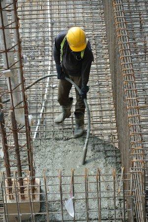 Construction Workers Using Concrete Vibrator
