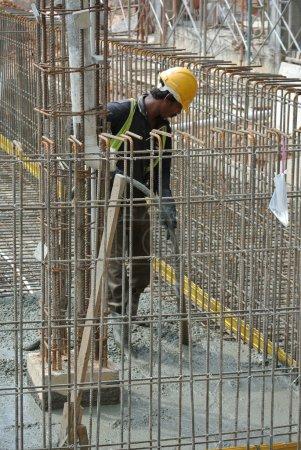 Photo pour Un ouvrier de la construction utilisant un vibromasseur en béton sur un chantier de construction à Selangor, Malaisie. Vibromasseur de béton est utilisé pour le compactage du nouveau béton a été coulé . - image libre de droit