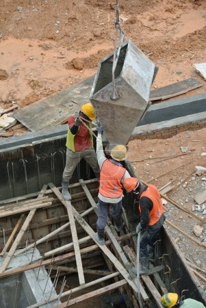 Group of construction workers casting reinforcement concrete wall