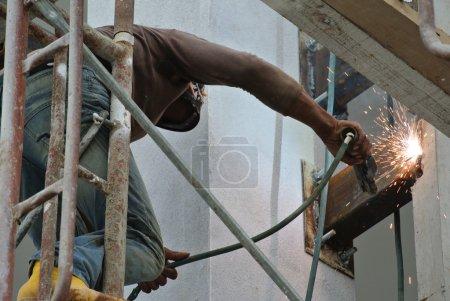 Photo pour Soudeurs prenant des risques très élevés travaillant à haut niveau sur le chantier . - image libre de droit