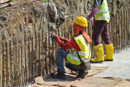 Photo pour Les travailleurs de la construction fabriquent des barres d'armature de mur de soutènement sur le chantier de construction . - image libre de droit