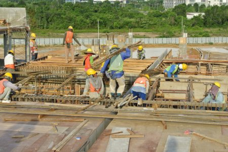 Group of construction workers fabricating floor slab and beam reinforcement bar and f ormwork