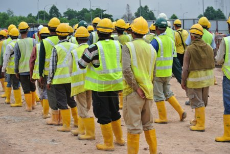 Group of construction workers assemble at the open...