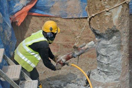 Photo pour Travailleurs de la construction à l'aide de béton hacker pour couper le pieu en béton sur le chantier à Cyberjaya, Malaisie le 20 mars 2015. - image libre de droit