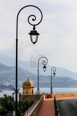 Antique lamp posts along a street with sea view in Monaco