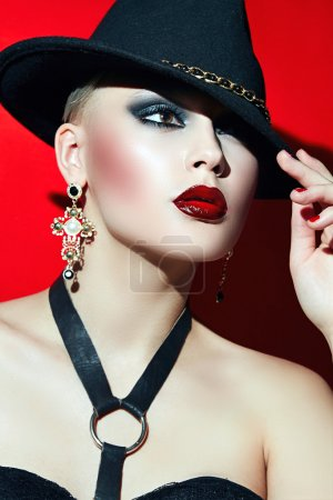 Photo for Rock girl in a black hat with red lips and dark eyes in a corset. Golden big earrings in the shape of a cross - Royalty Free Image