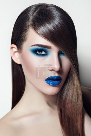 Girl with brown hair smooth silky straight hair and with blue ink and lipstick.