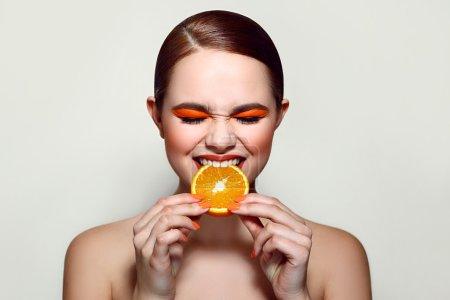 Sour orange. The girl is tasting the fruit.