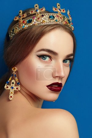 Girl with a golden crown and golden earrings.