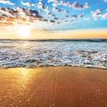 Colorful ocean beach sunrise with deep blue sky an...