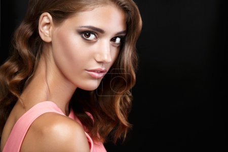 Beautiful woman in a pink romantic dress with smooth wavy hair and smoky eyes make up  on black background