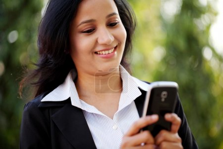 Happy young business woman texting at outdoors