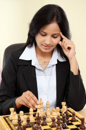 Young female business woman playing chess