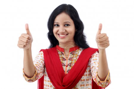 Photo for Happy young womanmaking thumbs up sign against white - Royalty Free Image