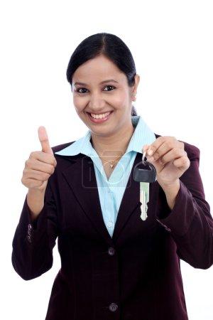 Heureuse jeune femme d'affaires tenant la clé