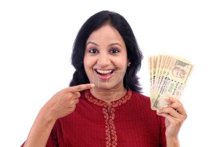 Photo pour Jeune femme excitée tenant cinq cents roupies contre blanc - image libre de droit