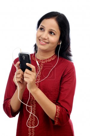 Young beautiful woman enjoying the music with smartphone