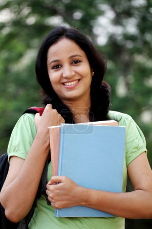 Happy young female student at college campus