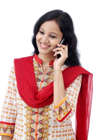 Beautiful young woman talking on mobile phone against white