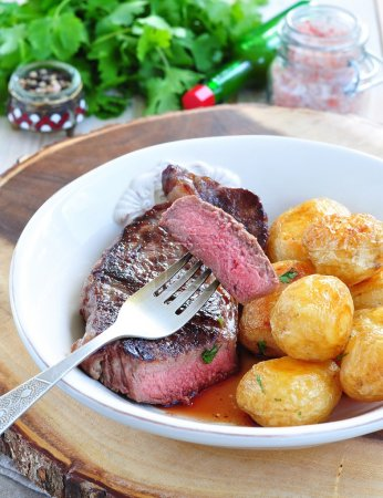 Photo for Medium rare grilled Beef steak with roasted potato - Royalty Free Image