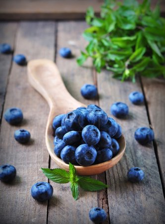 Photo for Organic fresh blueberries with peppermint on a wooden background - Royalty Free Image