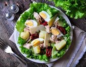 salad of lettuce, iceberg lettuce, with canned tuna, dried tomatoes, boiled potatoes, capers and parmesan cheese, dressed with olive oil. Selective focus. rustic style.