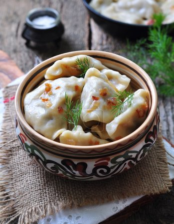 Dumplings with potatoes and mushrooms with fried onions in a traditional ceramic plate on a wooden table. Ukrainian traditional cuisine. rustic style. selective focus