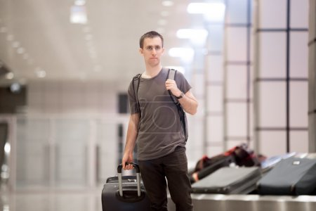 Traveller with luggage at conveyor belt
