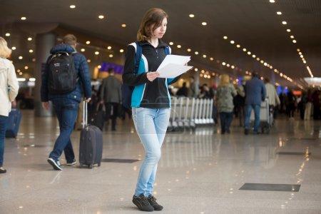 Photo pour Portrait de jeune femme avec sac à dos debout dans l'aérogare, avec billets électroniques imprimés, en utilisant un téléphone portable pour s'enregistrer, foule floue de voyageurs sur le fond - image libre de droit