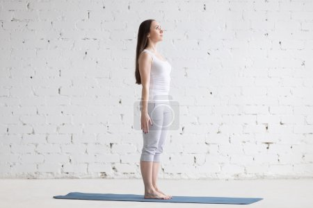 Photo for Attractive happy young woman working out indoors. Side view portrait of beautiful model doing yoga exercise on blue mat. Standing in Tadasana, Mountain Pose. Full length - Royalty Free Image