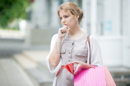 Pensive young woman out of cash after shopping