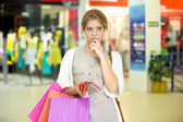 Pensive young woman holding empty wallet after shopping