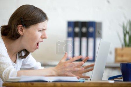 Photo pour Jeune femme d'affaires stressée assise avec un ordinateur portable et criant avec une expression en colère. Furieux homme d'affaires se sentant irrité tout en utilisant pc, gesticuler et crier. Émotion humaine négative - image libre de droit