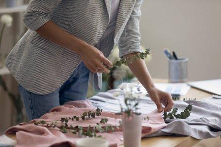 Photo pour Recadrer gros plan de designer de mode femme décorer nouvelle collection de vêtements avec des fleurs se préparer pour photoshoot dans le bureau. Femme créative moderne vêtements de style tailleur robes pour l'image ou le tir. - image libre de droit