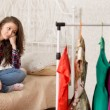 Girl choosing what to wear sits in front of hanger...