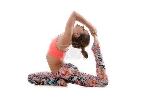Photo for Yoga girl on white background doing eka pada Rajakapotasana (King Pigeon Pose) - hands grasps feet - Royalty Free Image