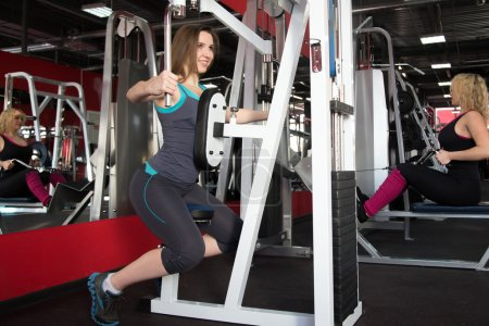 Photo pour Female clients of fitness center in sportswear training on apparatus in gym - image libre de droit